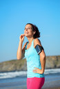 Fitness woman with sport band listening music joyful on beach during a break from running sporty girl wearing arm for smartphone Royalty Free Stock Image