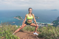 Fitness woman stretching her leg muscles doing side lunge exercise preparing for cardio work-out in mountains by the sea