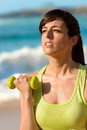 Fitness woman training arms working out on beach in summer sporty girl biceps hard with dumbbell sweaty sport caucasian female Royalty Free Stock Photos