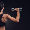 Fitness woman in training muscles of the back with dumbbells sporty pumping up and hands Royalty Free Stock Photo