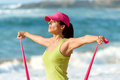 Fitness woman training shoulders exercising and with resistance band on summer girl sweating and working out on beach Stock Photos