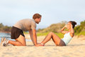 Fitness woman training situp crunches with trainer women personal instructor young couple happy working out in sand on beach Stock Photo