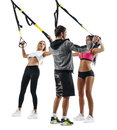 Fitness women do thrust with trx suspension with coach Royalty Free Stock Photo