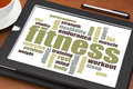 Fitness word cloud on a digital tablet with a cup of tea Royalty Free Stock Photo