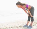Fitness young woman catching breathe after running on beach sandy Stock Photography