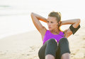 Fitness young woman doing abdominal crunch on beach