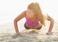 Fitness young woman doing push ups on beach sandy Stock Photos