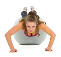 Fitness young woman doing push ups on fitness ball Royalty Free Stock Photo