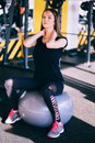 Fitness young woman in gym resting on Pilates ball Royalty Free Stock Photo