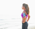 Fitness young woman in headphones looking into distance on beach rear view Stock Photo