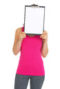 Fitness young woman holding blank clipboard in front of face isolated on white Royalty Free Stock Images