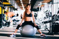 Fitness young woman with long hair in gym, sitting on Pilates ball Royalty Free Stock Photo