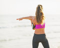Fitness young woman making exercise on beach rear view in sportswear Stock Photography
