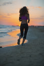 Fitness young woman running on beach at dusk rear view sandy Royalty Free Stock Image