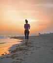 Fitness young woman running on beach in the evening rear view sportswear Royalty Free Stock Images