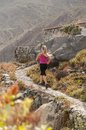 Fitness young woman running on a mountain road runner in beautiful nature caucasian female sport model jogging training Stock Photos