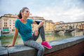 Fitness young woman sitting next to river with earphones Royalty Free Stock Photo