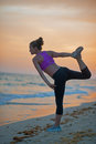 Fitness young woman stretching on beach in the evening sportswear Stock Images