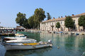 Fiume river mincio peschiera del garda italy view up the in in looking past moored small boats to the road bridge where the Stock Photography