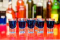 Five blue curacao alcoholic shots on bar with bottles background Stock Photo