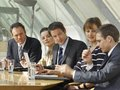 Five business executives sitting and discussing in a board room Stock Photos