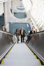 Five business people ascending escalator smiling front view portrait elevated view Stock Photo