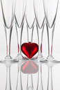 Five champagne glasses and red heart on a glass desk Royalty Free Stock Photo