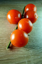 The five cherry tomatoes on the branch wooden background fresh red with drops of water green Stock Photography