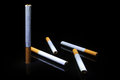 Five cigarettes on black background and reflecting surface Royalty Free Stock Photo