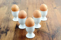 Five egg cups with natural brown eggs in arrow shape on table Royalty Free Stock Photos