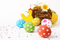 Five eggs decorated by hand easter coming out of a basket lies on a white background Stock Photo