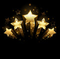 Five gold stars shining of foil on a black background Stock Images