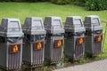 Five grey bin in the park Stock Photo