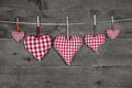 Five handmade red checkered hearts on wooden grey background white hanging a cord Royalty Free Stock Photography