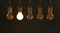 Five hanging vintage incandescent light bulbs with one illuminated Stock Photo