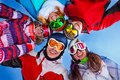 Five happy friends standing with goggles smiling in circle ski masks Stock Photos