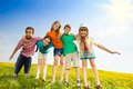 Five happy kids in the park boys and girls hugging together standing yellow flower field Stock Photography