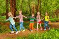 Five happy kids walking in forest holding hands Royalty Free Stock Photo