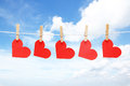 Five hearts on wooden pegs with blue sky background Stock Photos