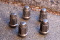 Five lug nuts for automobile from a car stand on a sidewalk Royalty Free Stock Photo