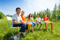 Five mates hold exercise books and sit in a row Royalty Free Stock Photo