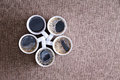 Five mugs full of black coffee ready to be served white porcelain fresh hot with bubbles arranged in a pentagon shape on a textile Stock Images