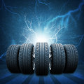 Five of new car wheels. Concrete wall, lightning Royalty Free Stock Photo