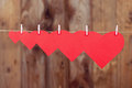 Five paper hearts hanging ascending on a rope on a wooden background with copy space Stock Photo
