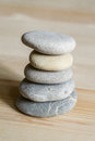 Five spa zen stones stacked on a wood background Royalty Free Stock Photo