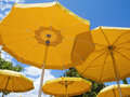 Five sunshades umbrellas in orange from below against the blue sky with small clouds Royalty Free Stock Images