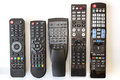 Five Used Remote Controls on White Background