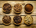 Five varieties of coffee beans and powder ground is separate dishes showing the different strengths colour the from Royalty Free Stock Photos
