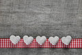 Five white hearts on an old grey wooden background with a checke checkered frame Stock Photo