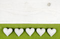 Five white hearts on wooden white shabby chic background with ap of stone apple green frame Royalty Free Stock Image